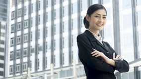 Asian business woman stands with confident posting at outdoor pu. The Asian business woman stands with confident posting at outdoor public space Royalty Free Stock Photos
