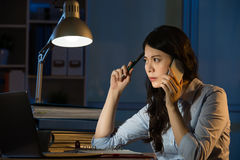 Asian business woman talk on smartphone working overtime Royalty Free Stock Photo