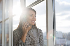Asian Business Woman Talking On Mobile Phone Call Standing in front Panoramic Window Businesswoman In Coworking Center Stock Photo