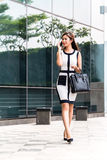 Asian business woman talking to cell phone outside stock photo