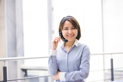 Asian Business woman talking using her headset in the office Royalty Free Stock Image