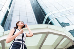 Asian business woman telephoning outside with  phone. Asian businesswoman telephoning wit smartphone in front of tower building Stock Photo
