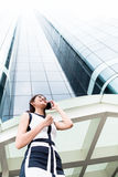 Asian business woman telephoning outside with  phone. Asian businesswoman telephoning wit smartphone in front of tower building Royalty Free Stock Photo