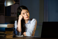 Asian business woman thinking and working overtime late night Royalty Free Stock Photography