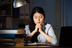 Asian business woman thinking and working overtime late night Royalty Free Stock Image