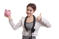 Asian business woman thumbs up with pig coin bank. Stock Photography