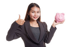 Asian business woman thumbs up with pig coin bank. Stock Image