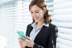 Asian business woman use phone. Young asian business woman use smart phone in the office stock photo