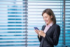 Asian business woman use smartphone. Young asian business woman use smart phone in the office royalty free stock image