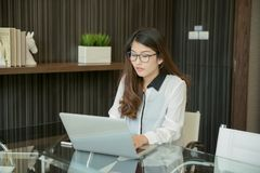 An Asian business woman using laptop in office stock image