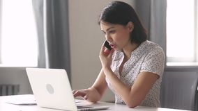 Asian business woman using laptop talking on phone in office stock video