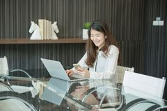 An Asian business woman using a phone in front of a laptop.  Royalty Free Stock Photos