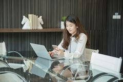 An Asian business woman using a phone in front of a laptop.  Royalty Free Stock Image