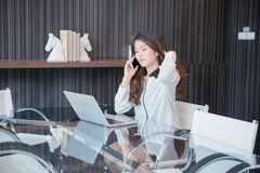 Asian business woman using a phone in front of a laptop.  Stock Photography