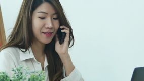 Asian business woman using phone for work in her home office. Enjoying time at home. Beautiful young smiling asian woman working on laptop while sitting in a stock video footage