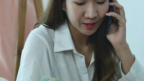 Asian business woman using phone for work in her home office. Enjoying time at home. Beautiful young smiling asian woman working on laptop while sitting in a stock footage