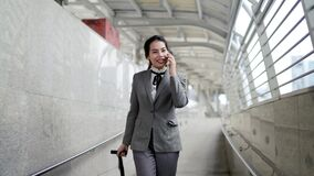 Asian Business woman walking outside the office and using tablet