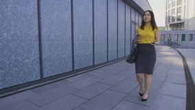 Asian business woman walking with phone and coffee. Beautiful young business woman in formal attire walking in business area during lunch break drinking coffee stock video
