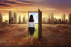 Asian business woman walking to the open wooden door with green Royalty Free Stock Photos