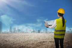 Asian business woman wear yellow helmet looking blueprint to bui Stock Photography