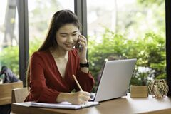 Free Asian Business Woman Wearing Red Dress Writing Down Requirement To Book And Talking With Customer In Smartphone Royalty Free Stock Photo - 174447585