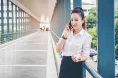 Asian business woman wearing white shirt talking smartphone for. Work Stock Photo