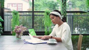 Asian business woman working document finance and calculator in her home office. Enjoying time at home. Beautiful young smiling asian woman working on laptop stock footage
