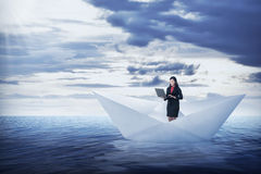 Asian business woman working with laptop on the paper boat Stock Photo