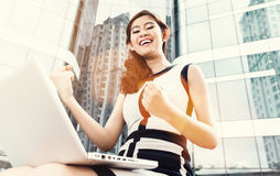 Asian business woman working outdoors with laptop. Om front of skyline reflection Stock Images