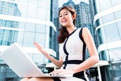 Asian business woman working outside on computer Royalty Free Stock Photo