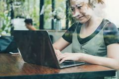 An asian business woman working and using laptop on wooden table in office with green nature background. Closeup image of an asian business woman working and royalty free stock photos