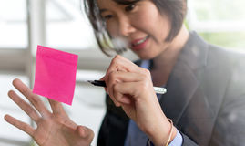 Asian business woman. Write on post it stic on transparent wall in brainstorm or planning work Royalty Free Stock Images