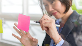 Asian business woman. Write on post it stic on transparent wall in brainstorm or planning work Royalty Free Stock Photo