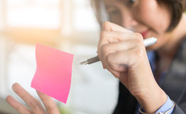 Asian business woman. Write on post it stic on transparent wall in brainstorm or planning work Royalty Free Stock Image