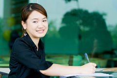 Asian business woman writing report Royalty Free Stock Images