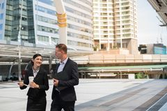 Asian business woman and Caucasian businessman walking together in the city and talk about business future. Asian business women and Caucasian businessman wear stock images