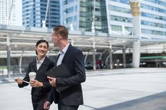 Asian business woman and Caucasian businessman walking in the city and talk about business future. Asian business women and Caucasian businessman wear suit stock image