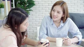 Asian business women enjoying drinking warm coffee, discuss about work and chit chat gossip while relax working in office. stock footage