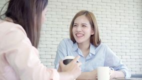 Asian business women enjoying drinking warm coffee, discuss about work and chit chat gossip while relax working in office. stock video footage