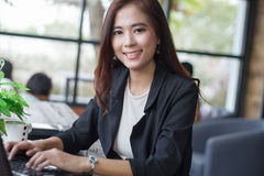 Asian business women using notebook and business women smiling h. Asian business woman using notebook and business woman smiling happy for working ,soft focus Royalty Free Stock Photos