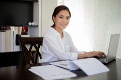 Asian business women using notebook and  smiling happy for worki. Asian business woman using notebook and  smiling happy for working Royalty Free Stock Photos