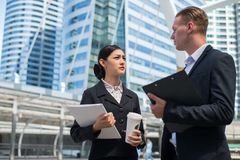 Asian business woman wear suit holding document file and plastic mug on hand talk about business future with Caucasian businessman. Asian business women wear royalty free stock images