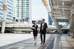 Asian business woman holding document file on hand and walking together with caucasian businessman in the city. Asian business women wear suit holding document stock photos