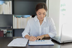 Asian Business women working and analysis graphics at office Stock Image