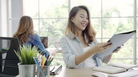 Asian business women working on computer while sitting on desk in smart casual wear at office. Asian business women working on computer while sitting on desk in stock footage