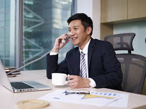 Asian businessman. Talking on phone in office Stock Images