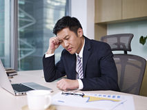 Asian businessman. Sitting and thinking in office, looking frustrated Stock Photo