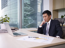 Asian businessman. Sitting and thinking in office, looking depressed Stock Images