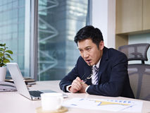 Asian businessman. Chewing on eyeglasses while thinking in office Royalty Free Stock Images
