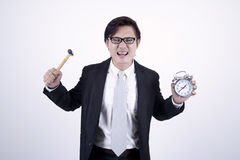 Asian businessman angry. With hummer and alarm clock isolated on white Stock Photography